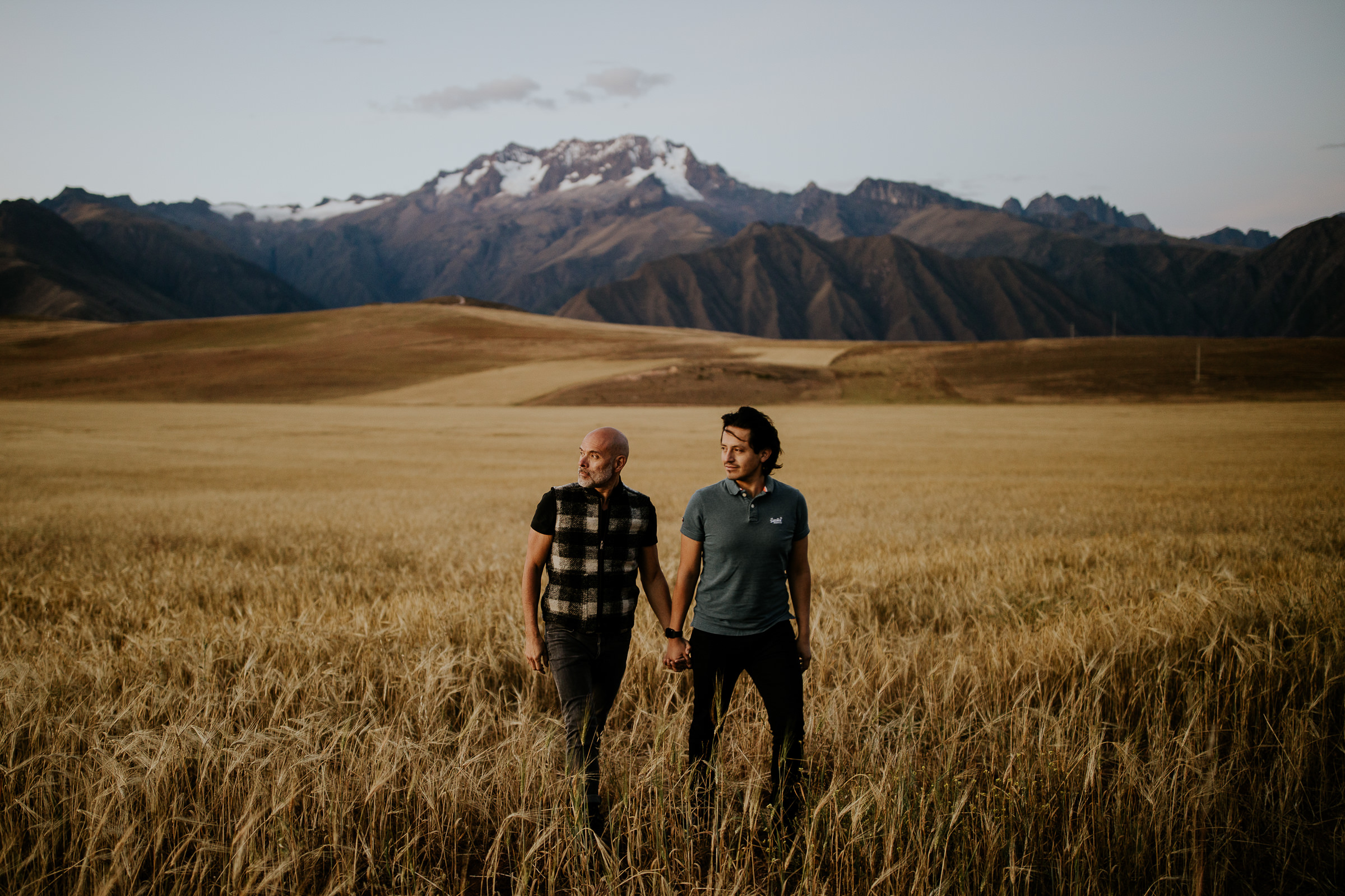two men holding hands in the fiel with mountains on back
