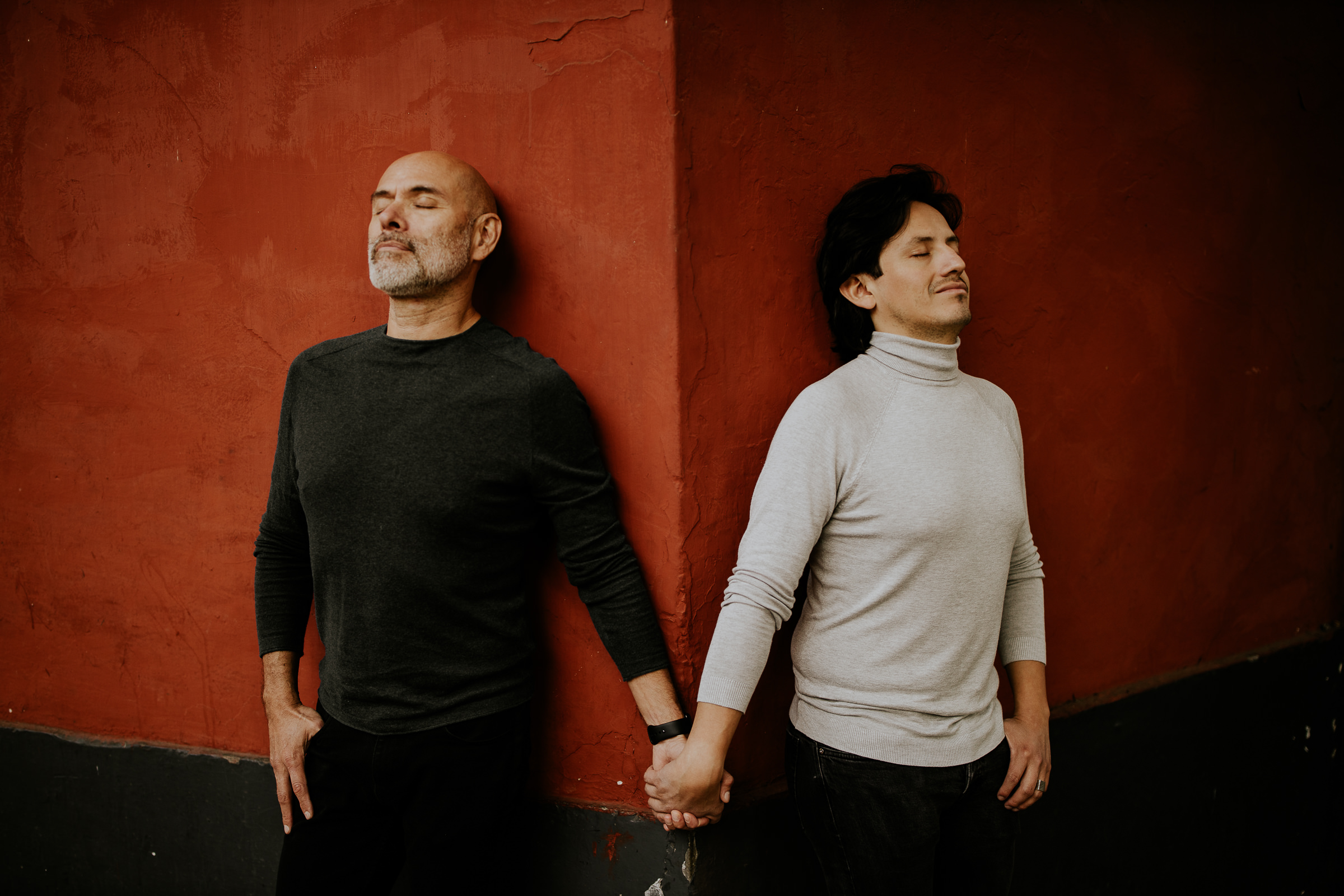 two men holding hands in front of a red wall