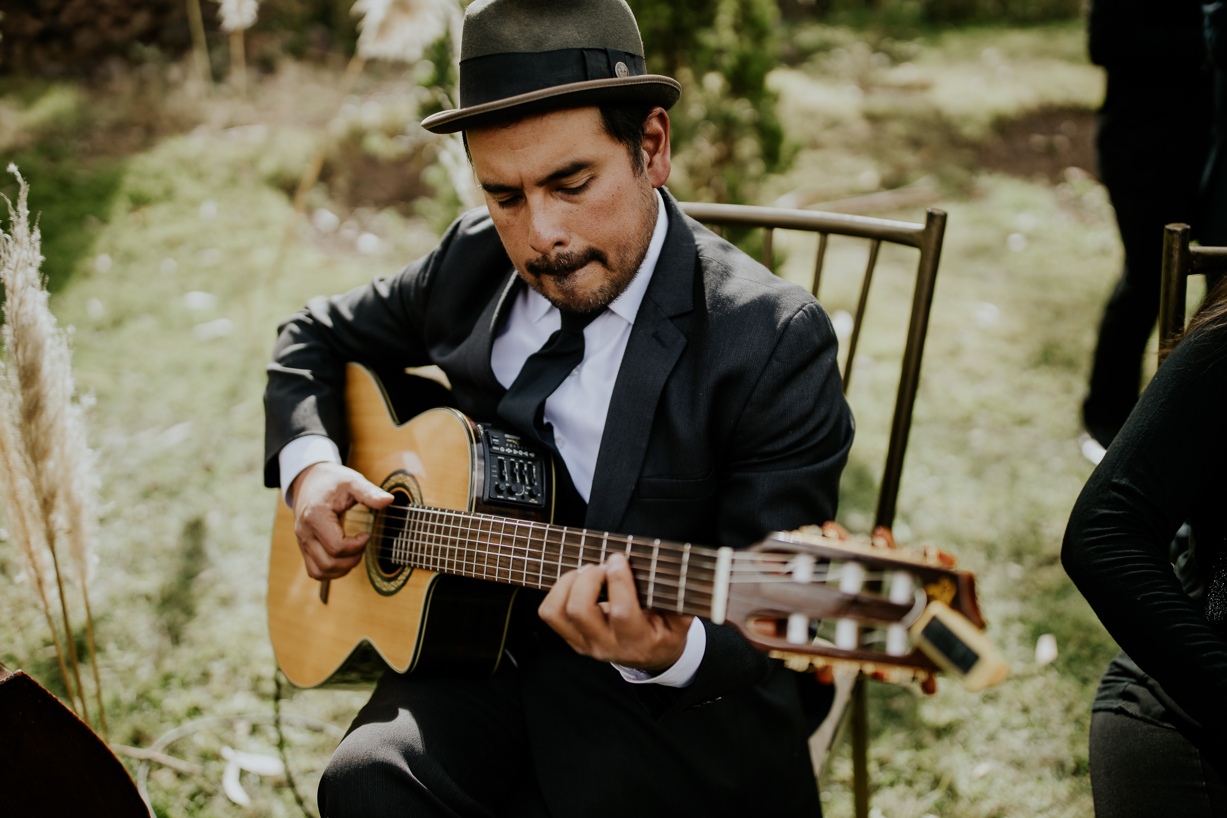 man playing guitar at a wedding ceremony