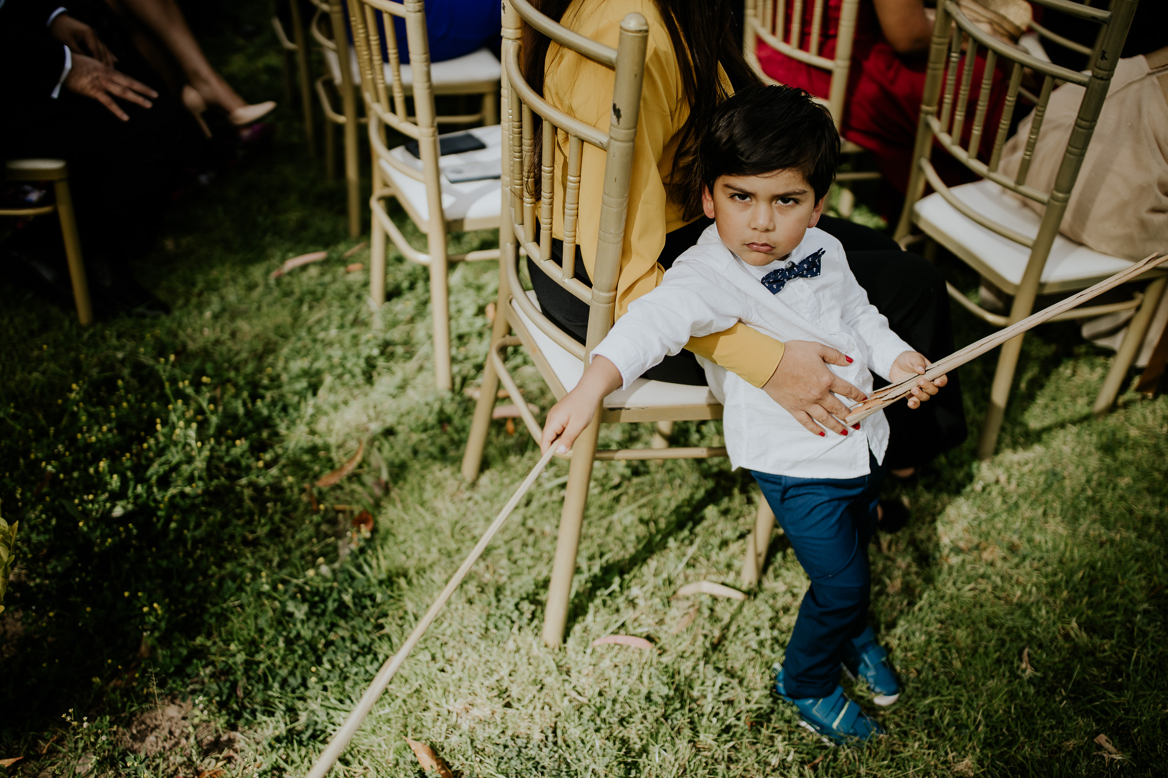 little boy holding a stick at a wedding ceremony