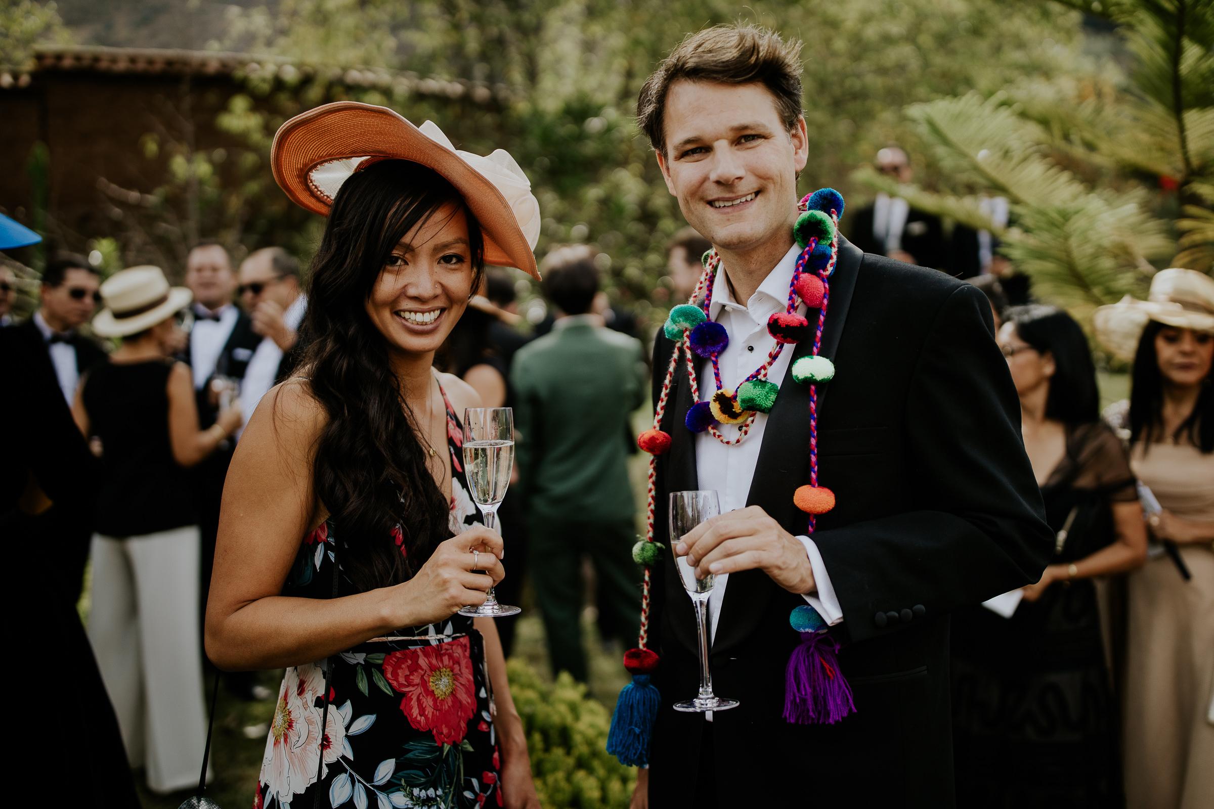 man and woman at a wedding cocktail look at the camera