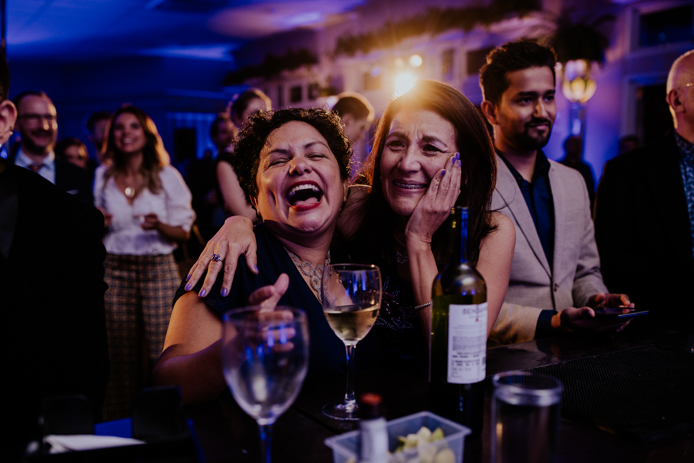 two women smiling while drinking wine at a wedding party
