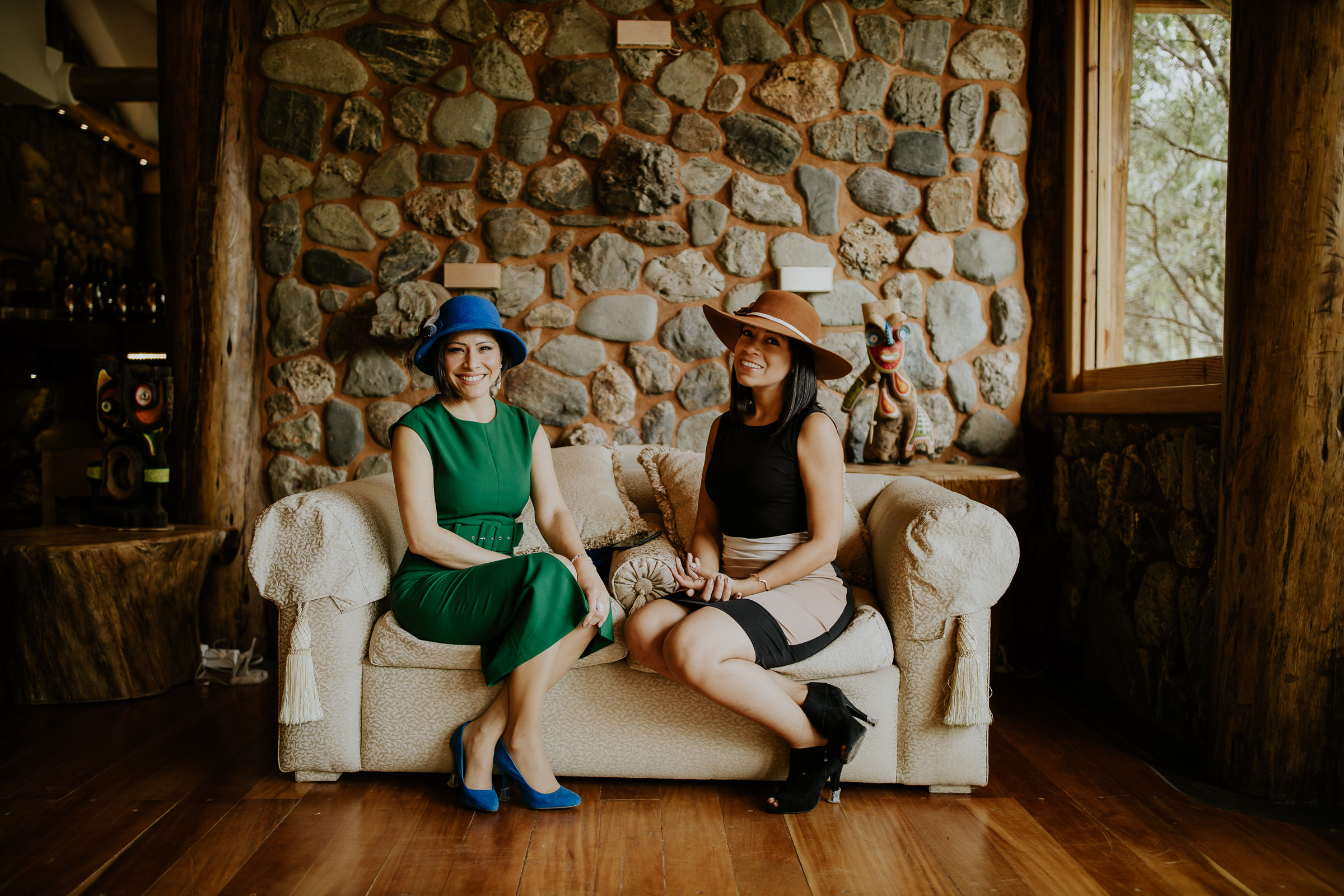 two women on a sofa with hats