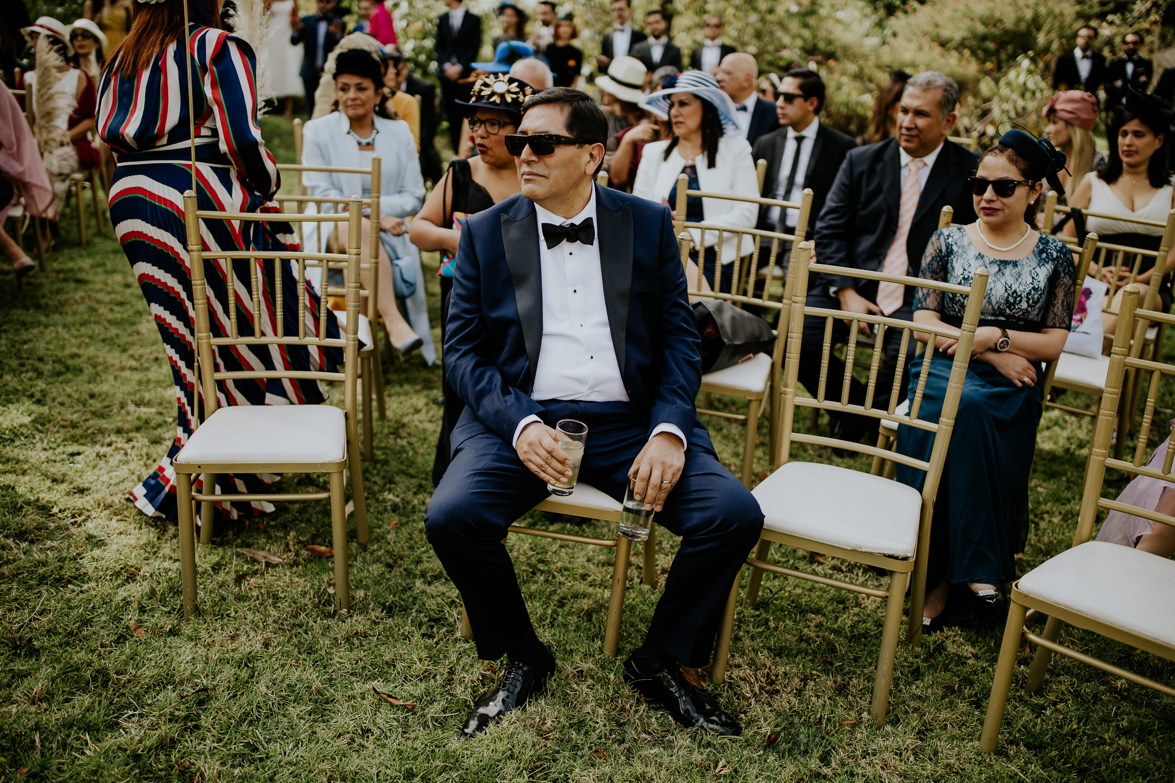 wedding ceremony guest holding two glasses