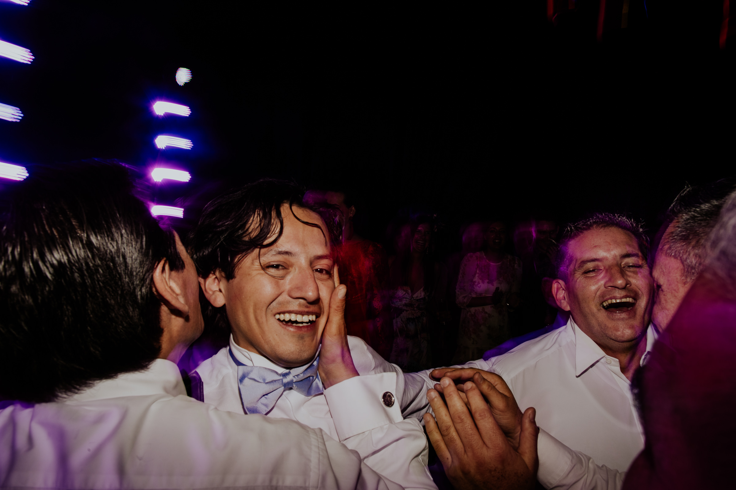 two men kissing at a wedding party